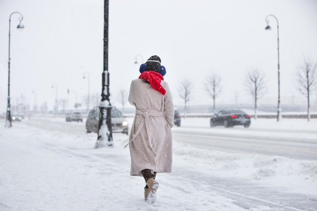 Trendy woman in beige coat, red scarf walking on empty street during snowfall