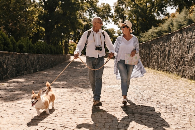Trendy woman in hat and blue blouse walking and looking grey haired man in white long sleeve shirt with camera and corgi in park.