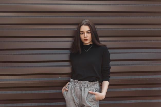 Модная женщина в модной черной одежде на улице