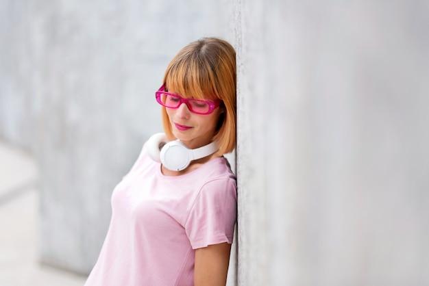 横方向のコピースペースで、満足の静かな笑顔で見下ろしている壁に向かってリラックスして立っているピンクのメガネのトレンディな女性