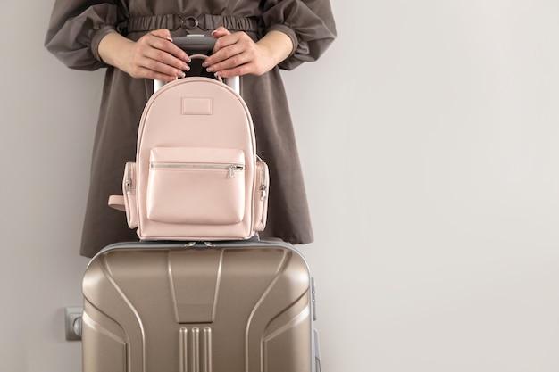 Модная женщина в плаще позирует с багажным чемоданом и рюкзаком готовится к деловой поездке