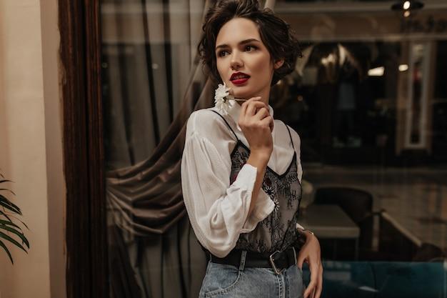 Donna alla moda in jeans con cintura e camicia bianca che tiene fiore all'interno. donna moderna con acconciatura corta e labbra luminose pose nella caffetteria.