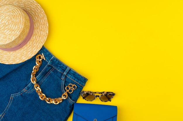 Trendy woman outfit with accessories on bright yellow surface