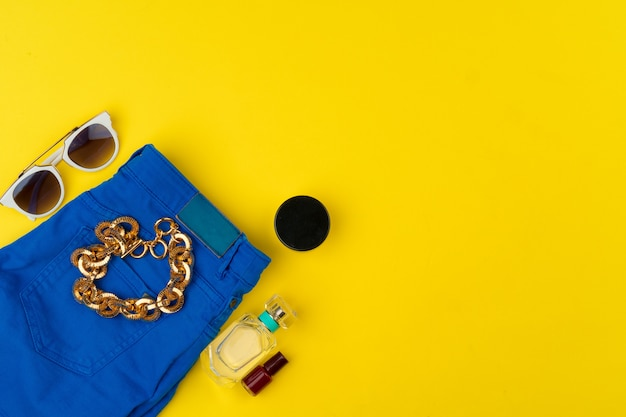 Trendy woman outfit with accessories on bright yellow table