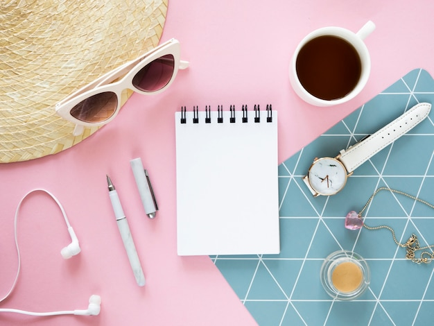 Trendy woman's desk top view mockup. opened notebook, straw hat and sunglasses. copy space for notes on a paper sheet.
