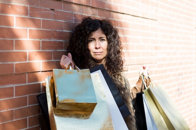 Trendy woman standing with shopping bags