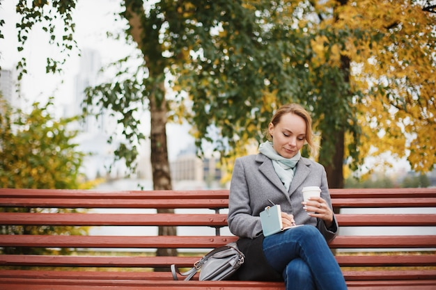 Trendy woman in stylish coat sitting on the bench in city park