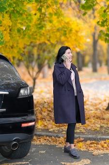 그녀는 화려한 단풍과 함께 가을 공원에서 그녀의 주차 된 차와 함께 서 그녀의 휴대 전화로 이야기하는 유행 여자