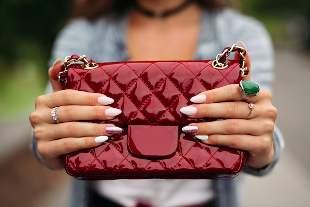 Trendy woman with beautiful manicure holding red handbag.
