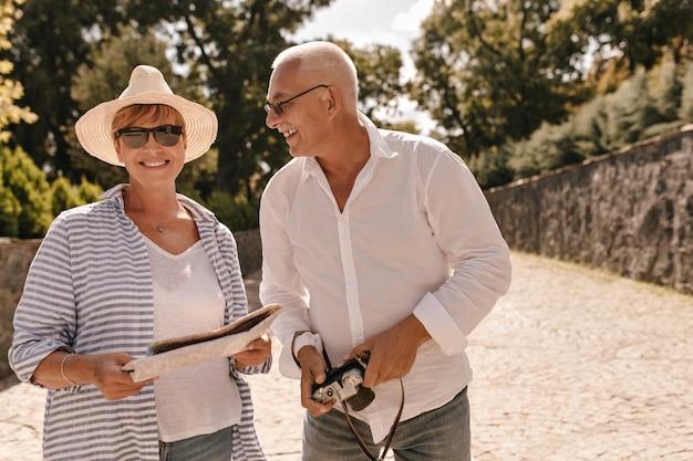 Donna alla moda con i capelli corti in cappello, occhiali da sole neri e camicetta a righe sorridente, tenendo la carta e in posa con un uomo dai capelli grigi con la macchina fotografica nel parco.