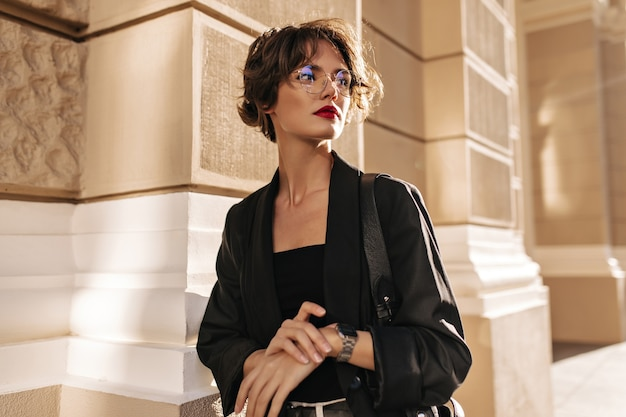 Trendy woman with wavy hairstyle and red lips posing outside. brunette woman in dark jacket and glasses looks away outdoors.