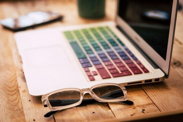 트렌디 한 나무 책상 사무실 또는 홈 워크 스테이션은 기술 노트북 컴퓨터와 닫습니다. elegante 안경-전화 장치 in. backgrund-사람들을위한 일과 직업의 개념