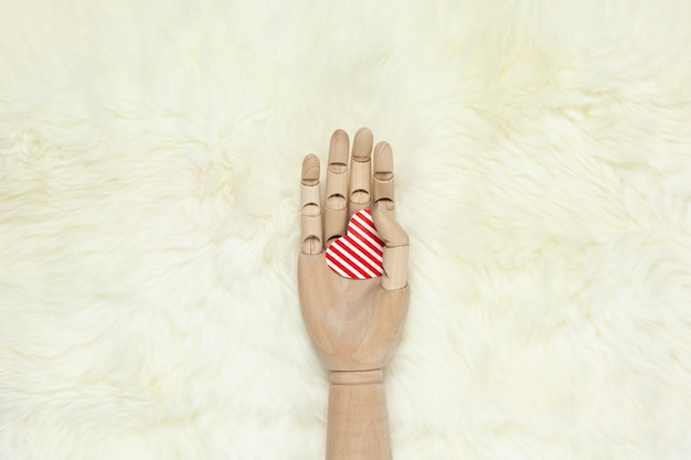 Trendy wooden hand holds red striped heart on white fur carpet