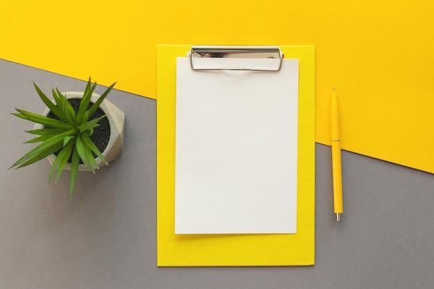 クリップボードペンのスマートフォンと黄色と灰色のオフィスのテーブルデスクに多肉植物のあるトレンディな職場 Premium写真