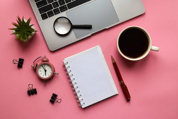 ノートパソコンのメモ帳ペン目覚まし時計プラント拡大鏡とコーヒーのトレンディな職場