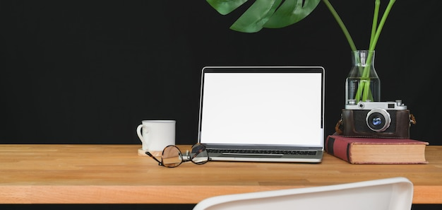 Trendy workspace with blank screen laptop computer and office supplies on wooden table
