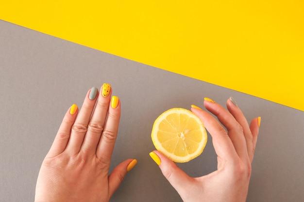 トレンディな黄色と灰色の女性のマニキュアレモンを持っている女性の手コピースペースでファッションと美容のコンセプト