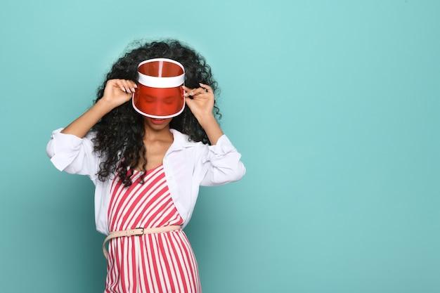 Модная молодая темнокожая женщина в полосатом платье с соответствующим красным винтажным козырьком или козырьком позирует, глядя на синий студийный фон с copyspace