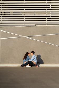 세련된 젊은 부부는 햇살 가득한 도시 거리의 롱보드에 앉아 행복한 미소를 지으며 함께 시간을 즐깁니다.