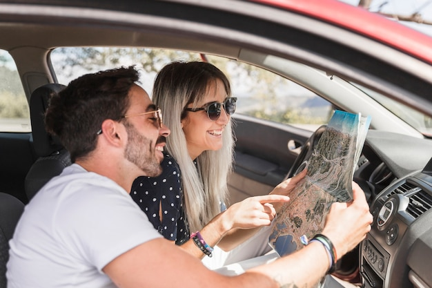 Trendy young couple sitting inside the car looking at map
