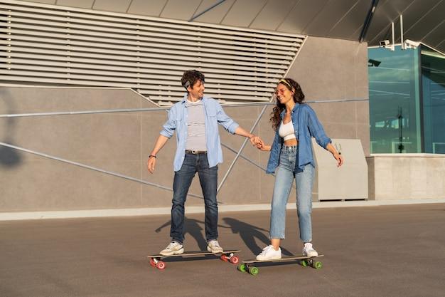 夏の街でスタイリッシュな男性と女性のロングボードを一緒にロングボードでスケートをするトレンディな若いカップル