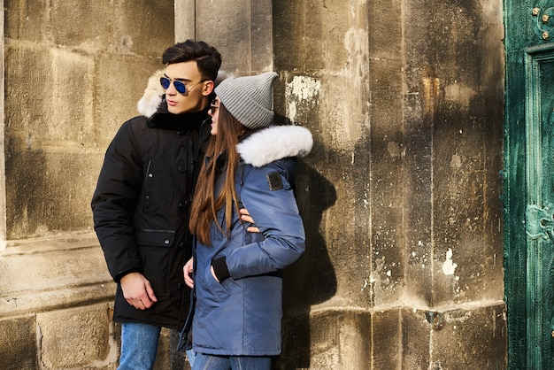 A trendy young couple walks in the city at christmastime