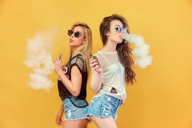 Trendy young friends in sunglasses and shorts standing and smoking