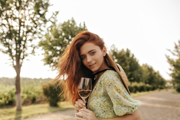 印刷された夏服と麦わら帽子の生姜の長いウェーブのかかった髪型のトレンディな若い女の子が正面を見て、屋外でワインとガラスを保持しています