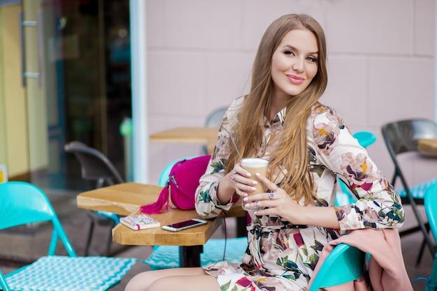 コーヒーを飲みながらカフェ春夏のファッショントレンドに座っているトレンディな若い流行に敏感なスタイリッシュな女性