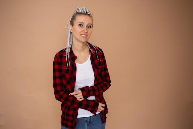 베이지 색 벽에 고립 된 험 상을 유행 젊은 hipster 여자