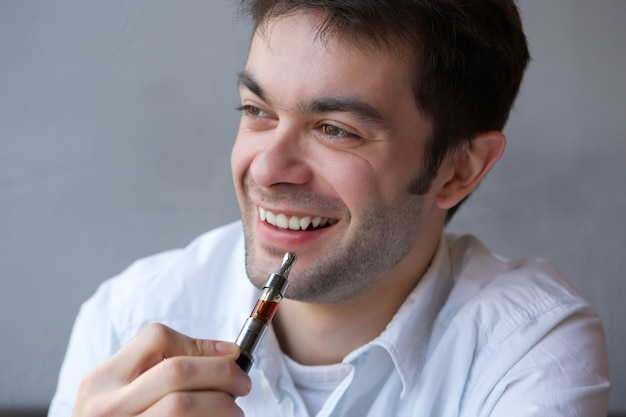 Trendy young man holding electric cigarette