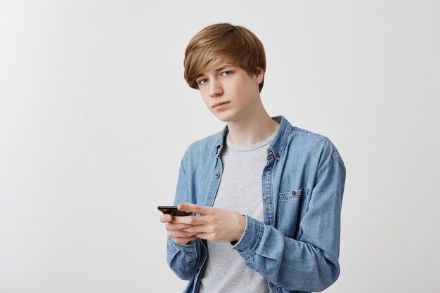 Trendy young man texts sms on smart phone to girlfriend, stands , enjoys free internet connection. male student in denim shirt types message to his parents, looks .