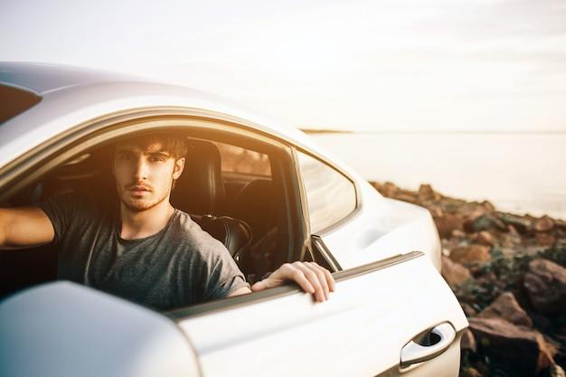 車で旅行するトレンディな若い男性。夏のロードトリップ旅行休暇でリラックスした幸せな男。