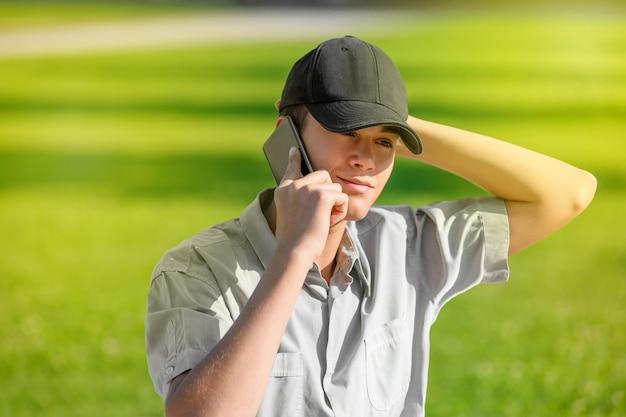 彼のスマートフォンを屋外で使うトレンディな若い10代の少年