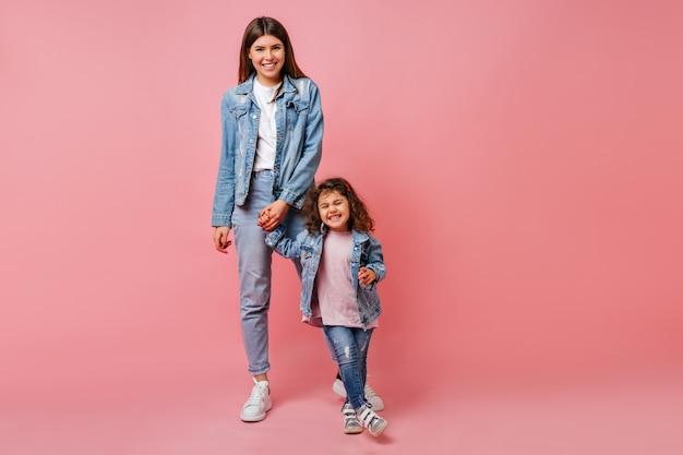 Alla moda giovane donna mano nella mano con la figlia riccia. studio shot di attarctive mamma e preteen kid ballare insieme.