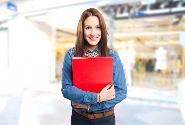Trendy young woman holding a red folder