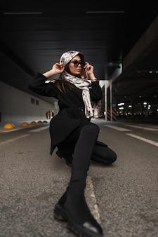 ブーツの頭にシルクのエレガントなスカーフとスタイリッシュな黒のコートのファッションサングラスのトレンディな若い女性は、街の駐車場のアスファルトに座っています。魅力的な女の子のファッションモデルは通りに休んでいます。