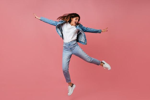 Trendy young woman jumping on pink background. full length view of carefree female model in denim outfit.