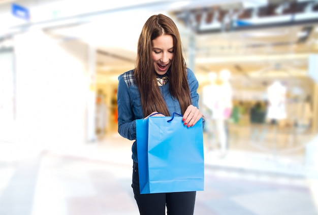 Trendy young woman looking surprised into a blue shopping bag