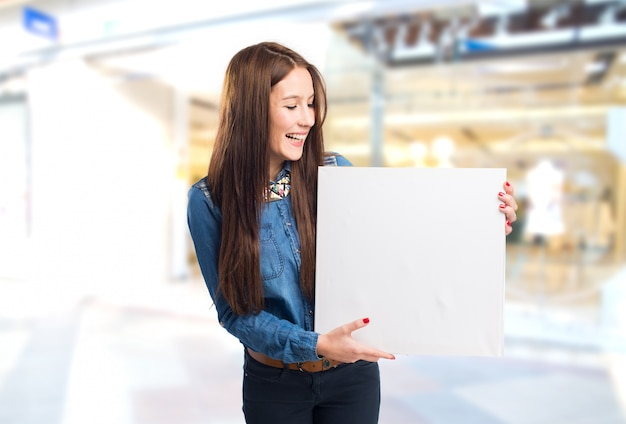 Trendy young woman showing a white canvas