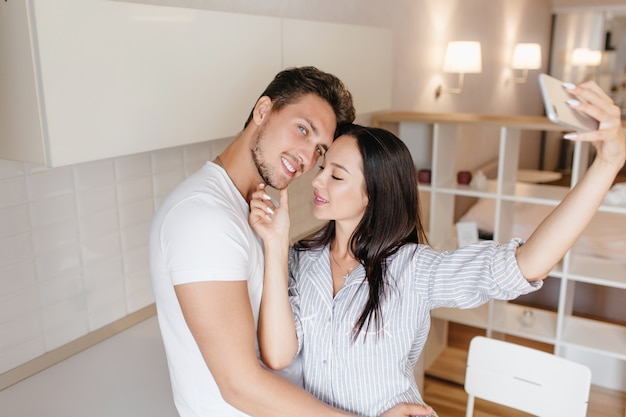 Trendy young woman in striped male shirt making selfie, gently touching husband's face