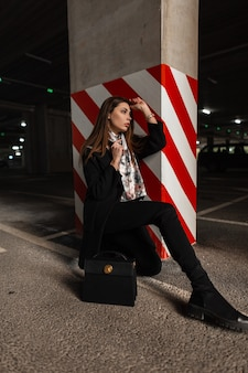 Trendy young woman in stylish black coat with silk elegant scarf in boots with leather handbag sits on the asphalt in parking lot near pillar in a red-white lines. attractive girl fashion model rests.