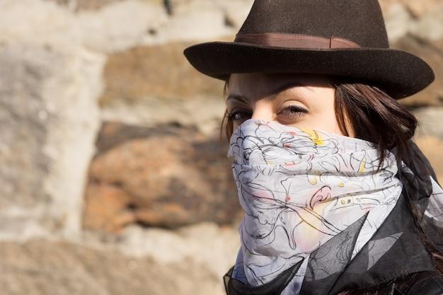 盗賊のように彼女の顔にスカーフとコピースペースのある石の壁に対してカメラを横から見ているスタイリッシュな帽子を身に着けているトレンディな若い女性