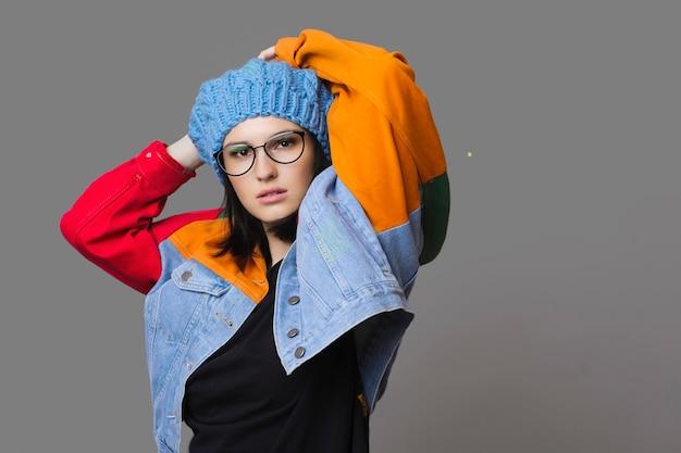 베레모와 안경 회색에 제기 팔 포즈와 화려한 세련된 재킷을 입고 유행 젊은 여자