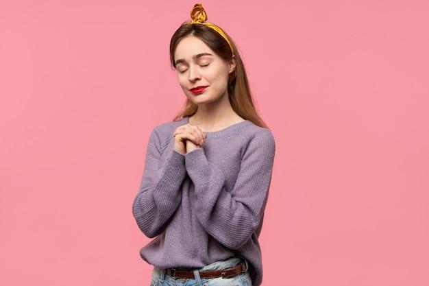 孤立したポーズと祈りの長い緩い髪を持つトレンディな若い女性