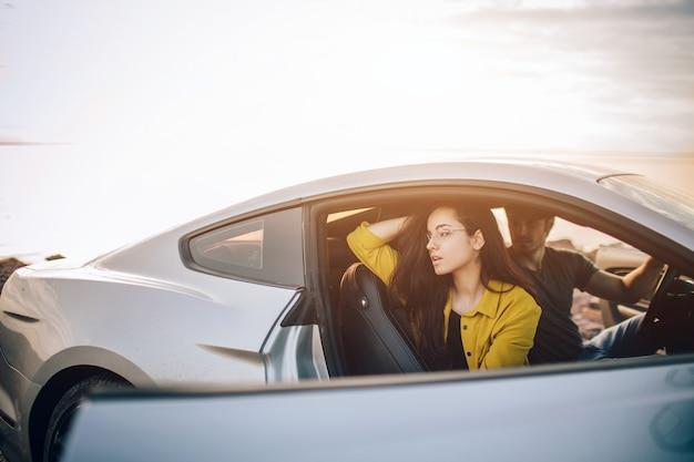 トレンディな若い女性と車で旅行する男性。夏のロードトリップ旅行休暇でリラックスした幸せなカップル。