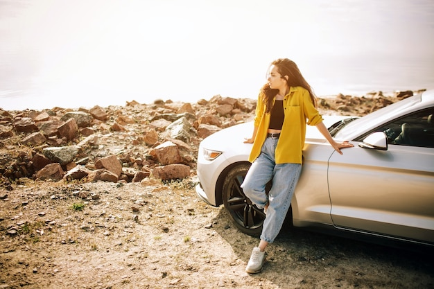 車で旅行するトレンディな若い女性。夏のロードトリップ旅行休暇でリラックスした幸せな女性。