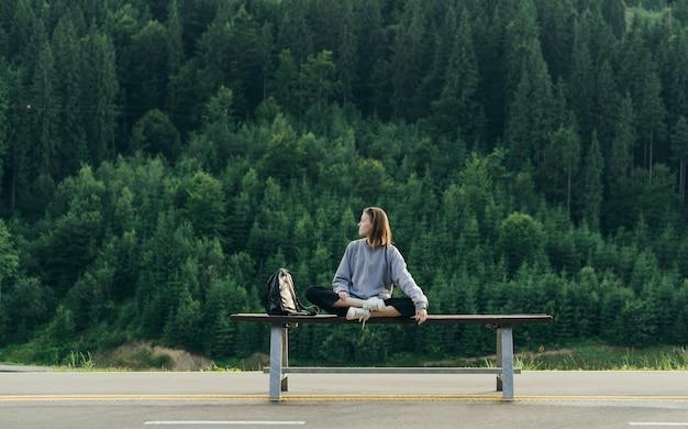 針葉樹林のバックパックを持つトレベラーの女の子
