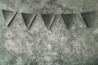Triangle black decorative flags hanging on grey background