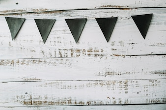 Triangle black flags hanging on painted wooden background